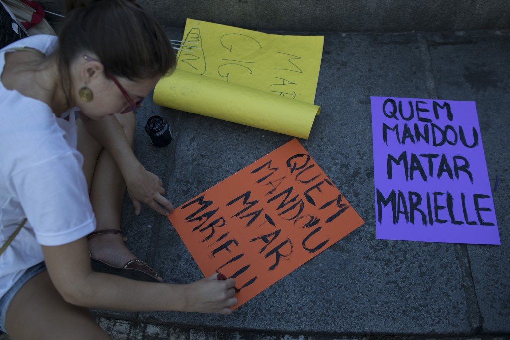"""A woman paints signs reading in Portuguese """"Who ordered Marielle's killing?"""" during a memorial for murdered councilwoman Marielle Franco and her drive"""