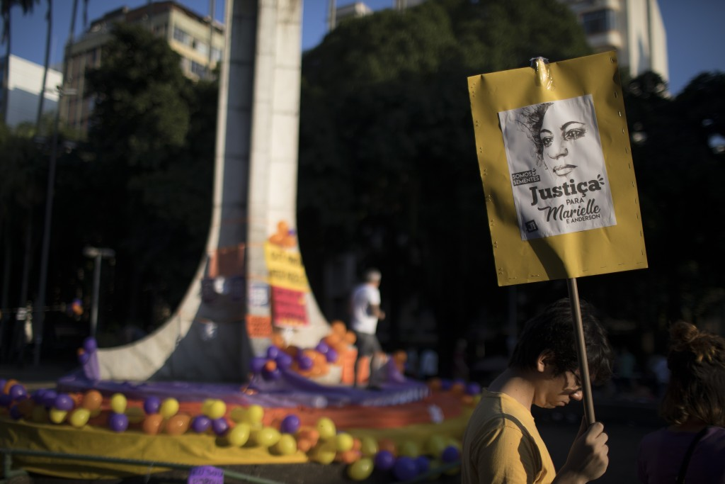 """A man holds sign with an image of murdered councilwoman Marielle Franco, with text written in Portuguese that reads """"Justice for Marielle and Anderson"""