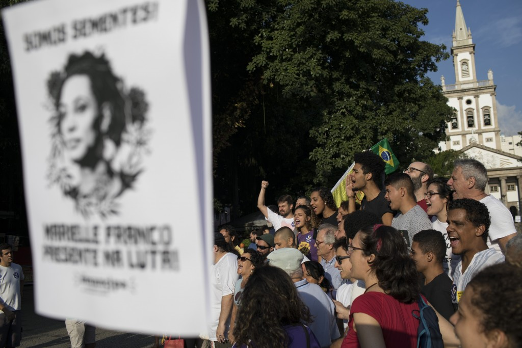 """People shout in Portuguese """"Marielle present"""" during a memorial for murdered councilwoman Marielle Franco and her driver Anderson Pedro Gomes, who bot"""