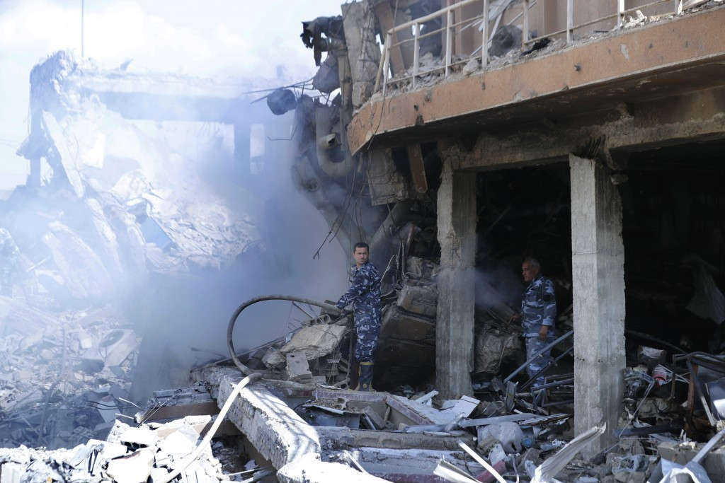 Firefighrers extinguish smoke that rises from the damage of the Syrian Scientific Research Center which was attacked by U.S., British and French milit