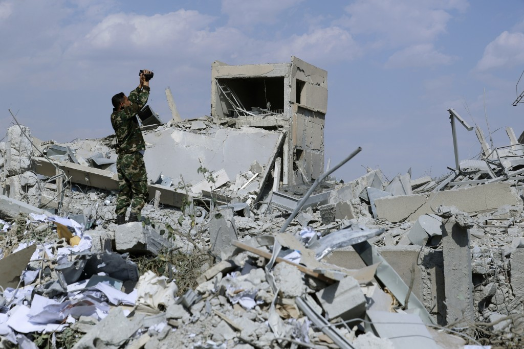 A Syrian soldier films the damage of the Syrian Scientific Research Center which was attacked by U.S., British and French military strikes to punish P