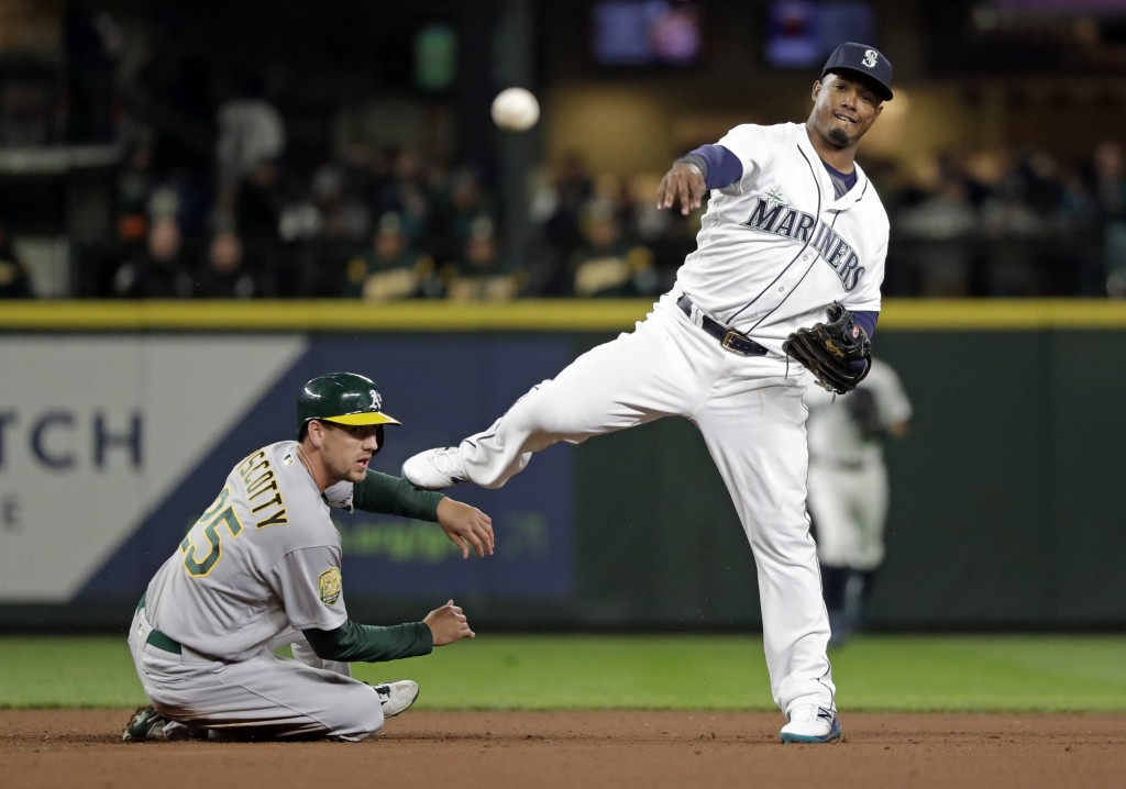 Seattle Mariners shortstop Jean Segura, right, throws to first after forcing out Oakland Athletics' Stephen Piscotty at second base during the fourth ...