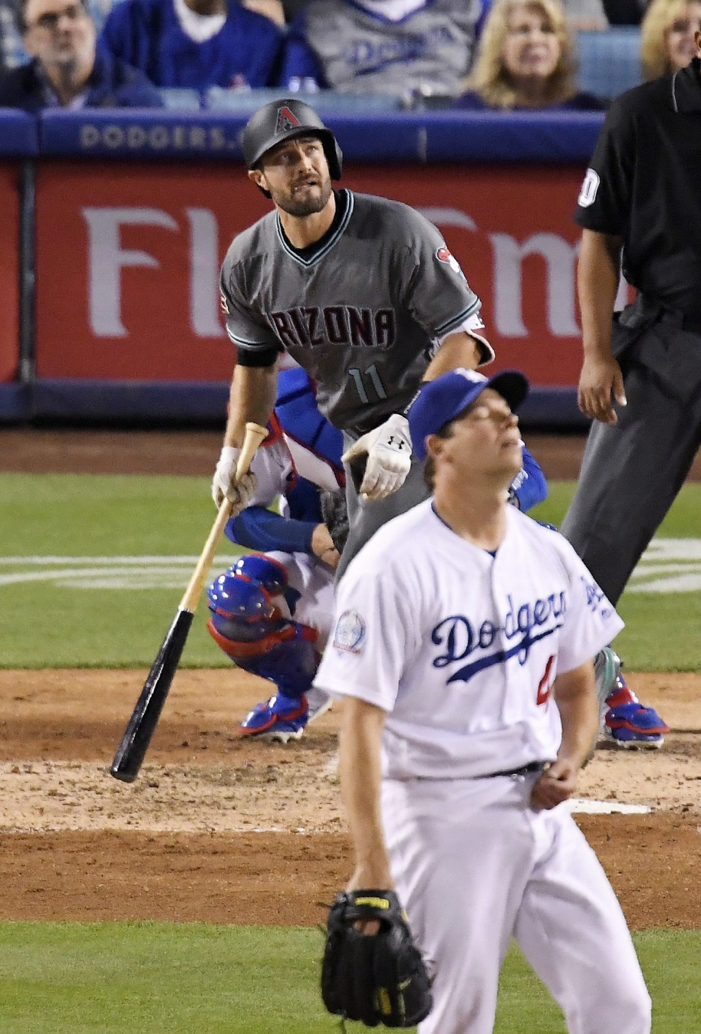 Arizona Diamondbacks' A.J. Pollock watches his two-run home run off Los Angeles Dodgers starting pitcher Rich Hill, foreground, during the fifth innin