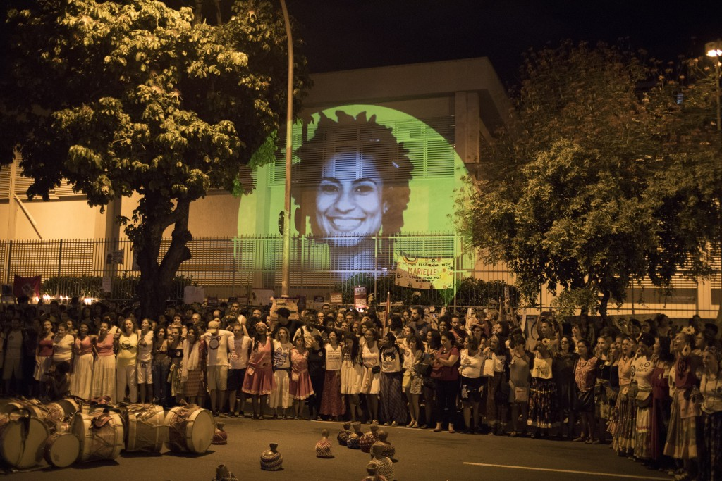 Backdropped by an image of councilwoman Marielle Franco projected on a wall, people gather in protest at the site where Franco and her driver Anderson