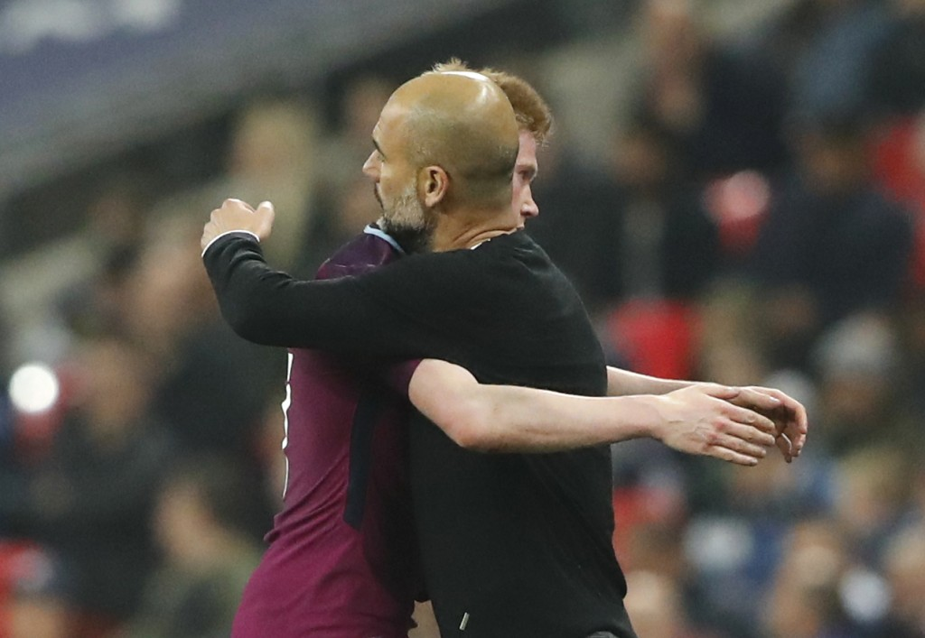 Manchester City manager Pep Guardiola embraces with Kevin De Bruyne during the English Premier League soccer match between Tottenham Hotspur and Manch...
