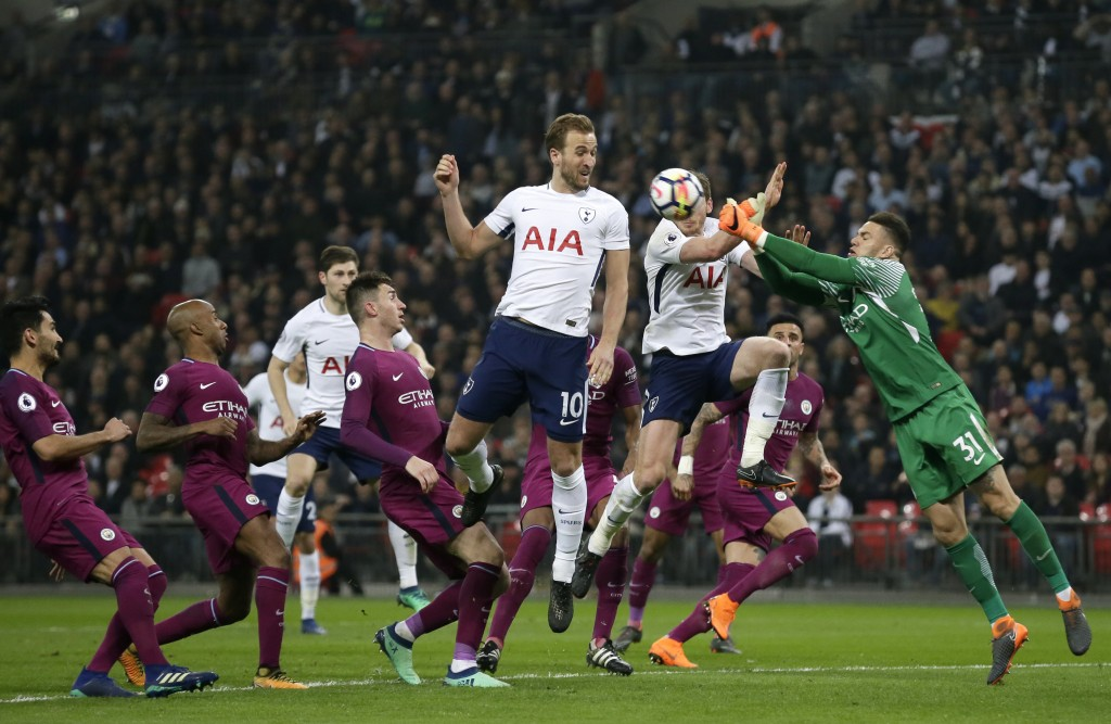 Manchester City goalkeeper Ederson, right, punches the ball away from Tottenham's Harry Kane, center, and Jan Vertonghen during the English Premier Le