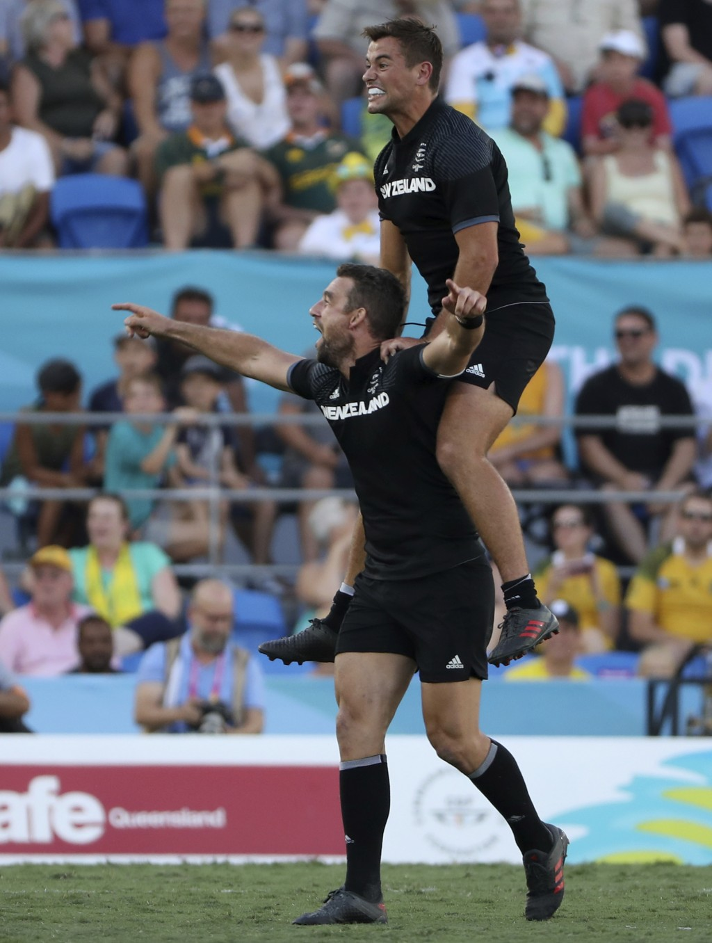 New Zealand's Kurt Baker, left, and Andrew Knewstubb celebrate after defeating Fiji to win their rugby sevens gold medal match at Robina Stadium durin