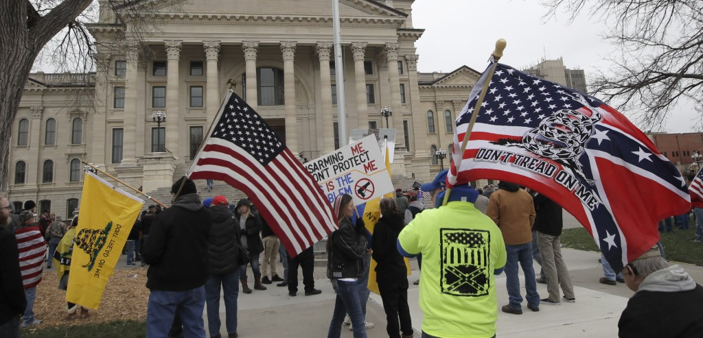 Flags wave at a pro-gun rally at the Kansas Statehouse in Topeka, Kan., Saturday, April 14, 2018. The rallies come less than three weeks after hundred