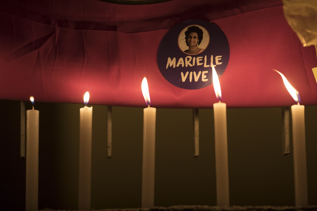 "Candles light a sticker with a picture of councilwoman Marielle Franco, that reads in Portuguese ""Marielle Lives,"" on the site where she and her drive"