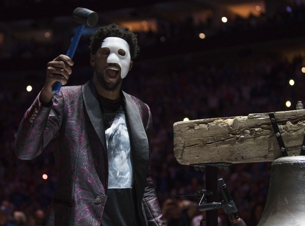 """Philadelphia 76ers' Joel Embiid comes out in a """"Phantom of the Opera"""" mask as he rings a Liberty Bell replica before Game 1 of the team's first-round"""