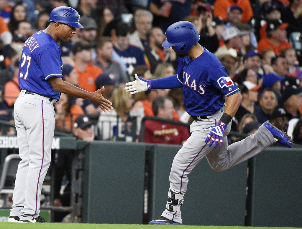Texas Rangers' Isiah Kiner-Falefa, right, shakes hands with third base coach Tony Beasley after hitting a solo home run off Houston Astros starting pi