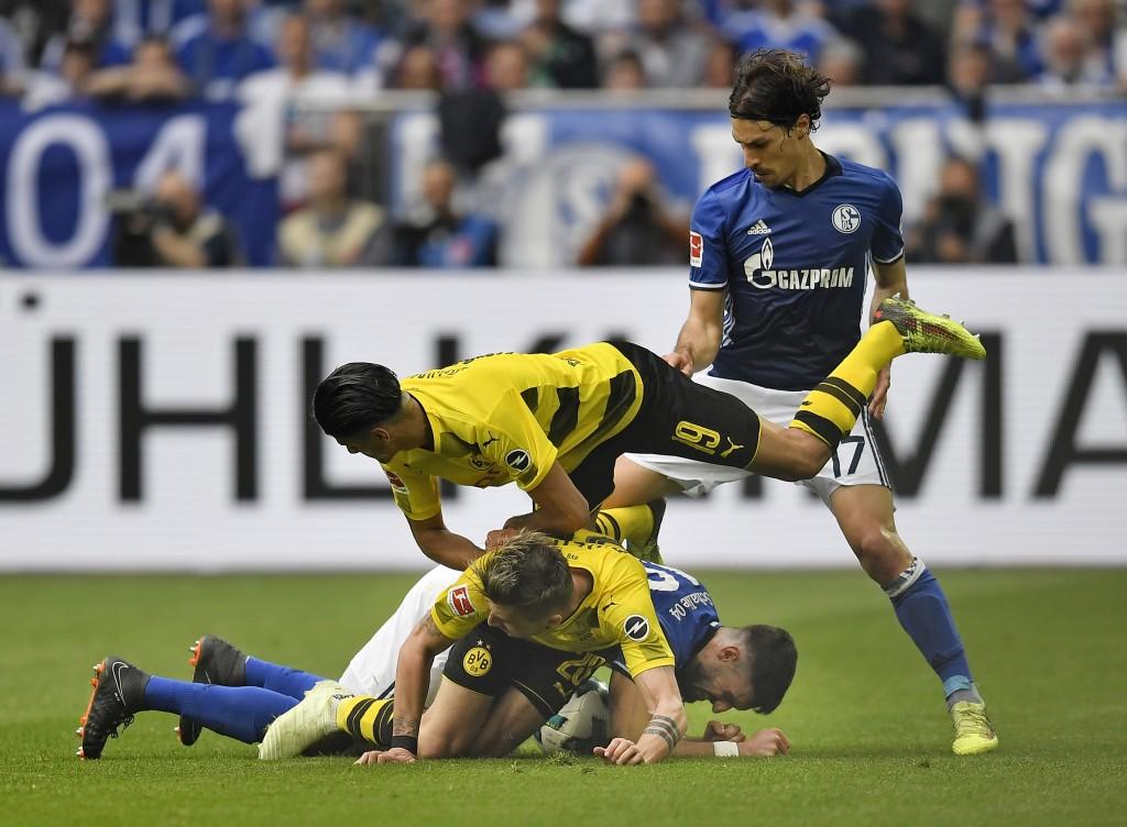 Schalke's Daniel Caligiuri, Dortmund's Mahmoud Dahoud, Dortmund's Lukasz Piszczek and Schalke's Benjamin Stambouli challenge for the ball during the G
