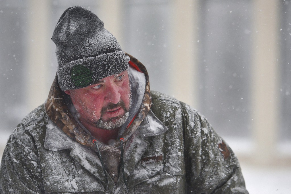 James Schoenhard, with Schoenhard Lawn Care, plows sidewalks with his team downtown Saturday, April 14, in Sioux Falls, S.D.  A storm system stretchin