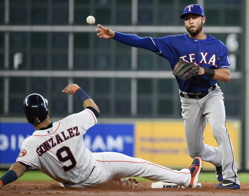 Texas Rangers second baseman Isiah Kiner-Falefa, right, turns a double play over Houston Astros' Marwin Gonzalez (9) to end the third inning of a base