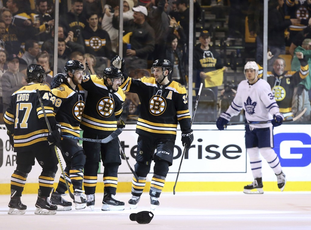 As Toronto Maple Leafs' Auston Matthews, right, skates away, Boston Bruins' David Pastrnak (88) is congratulated by Torey Krug (47), Brad Marchand and
