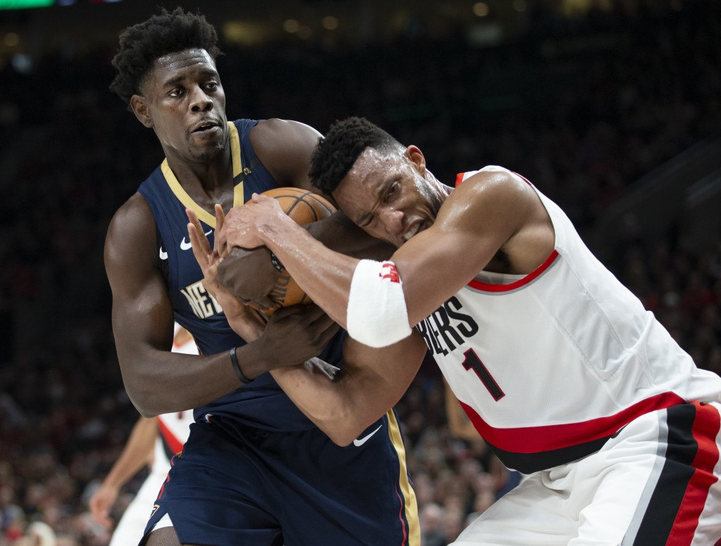 New Orleans Pelicans guard Jrue Holiday and Portland Trail Blazers forward Evan Turner vie for the ball during the first half in Game 1 of an NBA bask