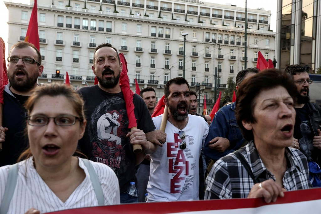 Supporters of the Greek Communist party chant slogans during an anti-war rally in front of the parliament, in Athens, Saturday, April 14, 2018. Thousa