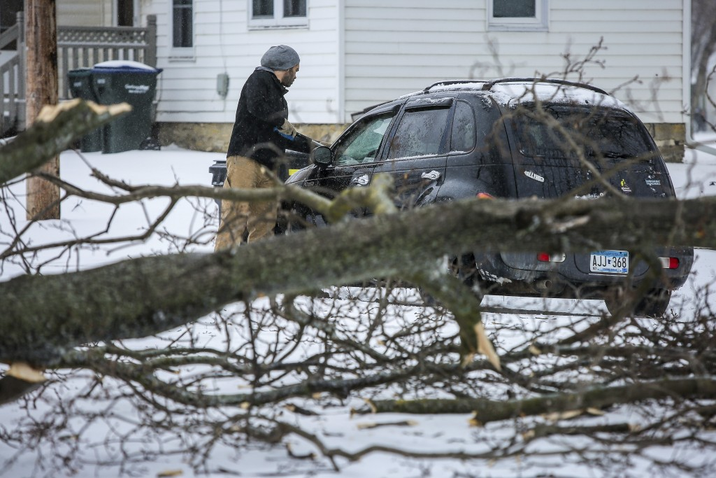 Lee Rinehart scrapes snow and ice off of his vehicle near where a large tree branch had fallen during a storm Saturday, April 14, 2018, in Rochester,