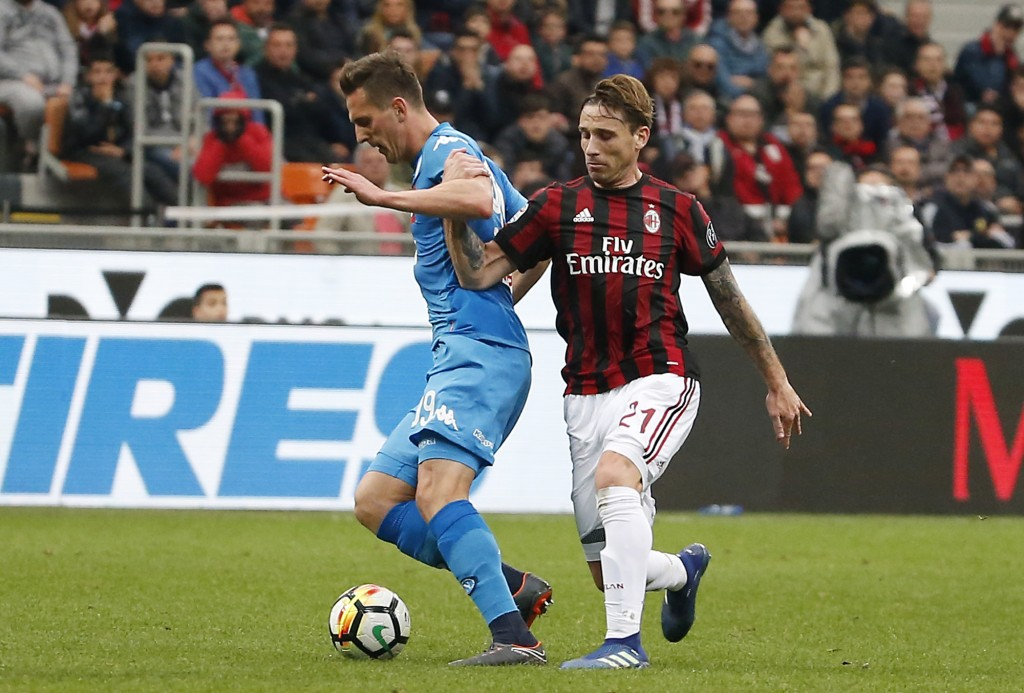 AC Milan's Lucas Biglia, right, challenges for the ball with Napoli's Arkadiusz Milik during the Serie A soccer match between AC Milan and Napoli at t