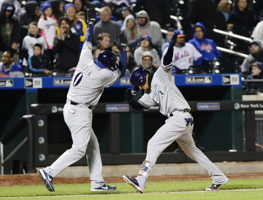 Milwaukee Brewers' Orlando Arcia (3) celebrates with third base coach Ed Sedar (0) while running the bases after hitting a home run during the ninth i