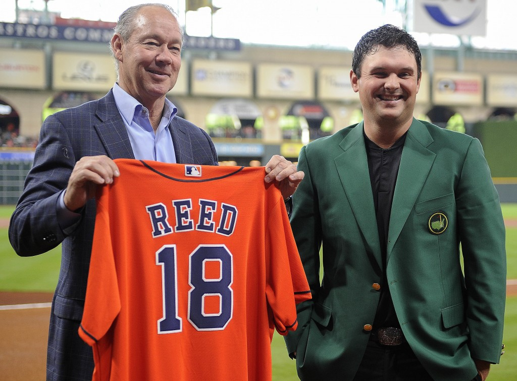 Houston Astros' owner Jim Crane, left, presents 2018 Masters champion Patrick Reed with a Houston Astros jersey before a baseball game against the Tex