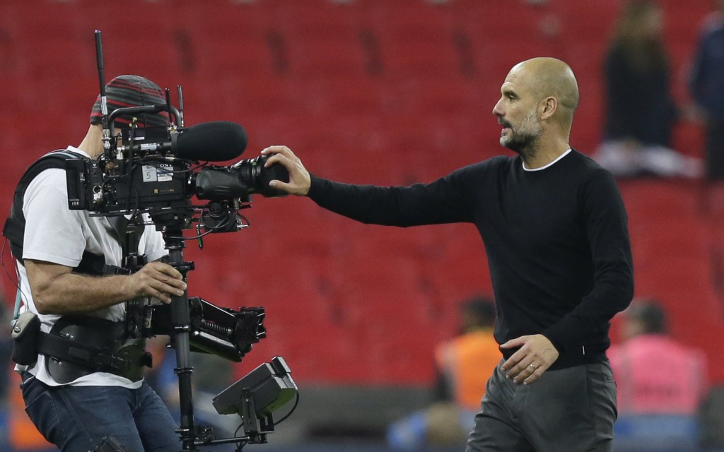 Manchester City coach Pep Guardiola covers a video camera with his hand as he leaves the field at the end of the English Premier League soccer match b