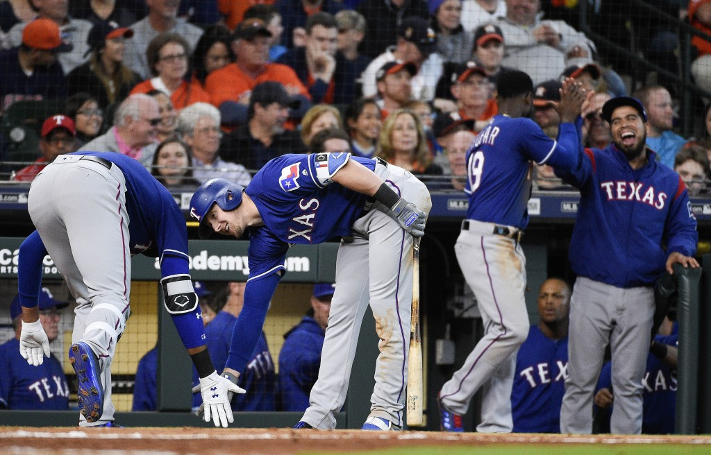 Texas Rangers' Ronald Guzman, left, celebrates his game-tying home run off Houston Astros relief pitcher Brad Peacock with Ryan Rua during the eighth