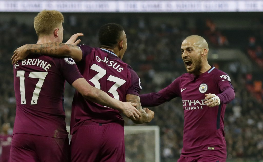 Manchester City's Gabriel Jesus celebrates with Kevin De Bruyne, left, and David Silva, right, after scoring the opening goal during the English Premi
