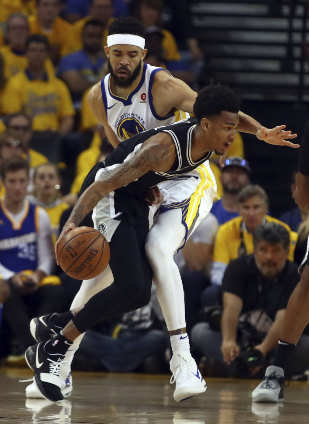 San Antonio Spurs' Dejounte Murray, right, drives the ball around Golden State Warriors' JaVale McGee (1) during the first half in Game 1 of a first-r