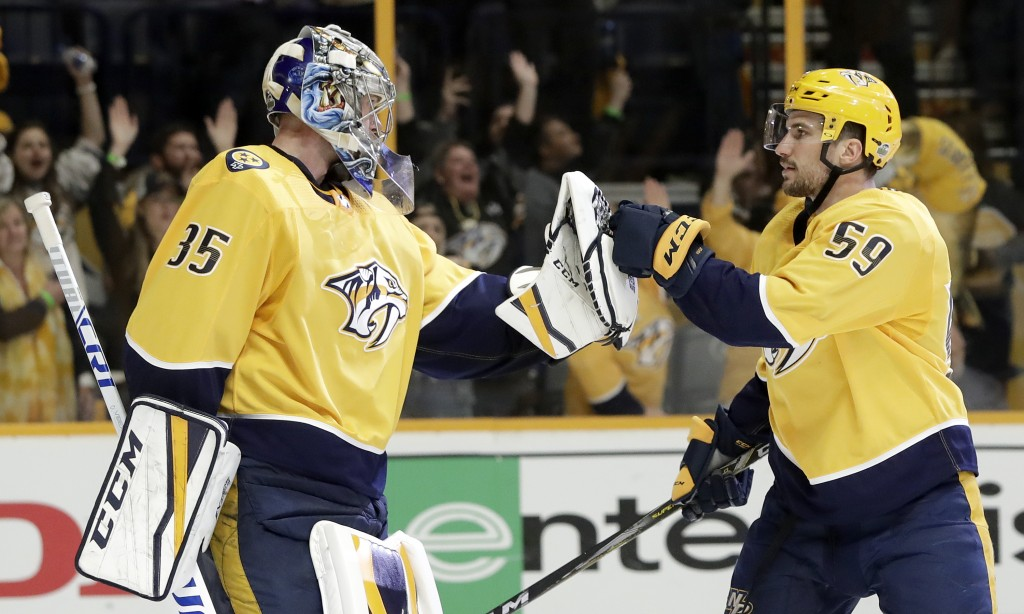 Nashville Predators goalie Pekka Rinne (35), of Finland, and defenseman Roman Josi (59), of Switzerland, celebrate after beating the Colorado Avalanch
