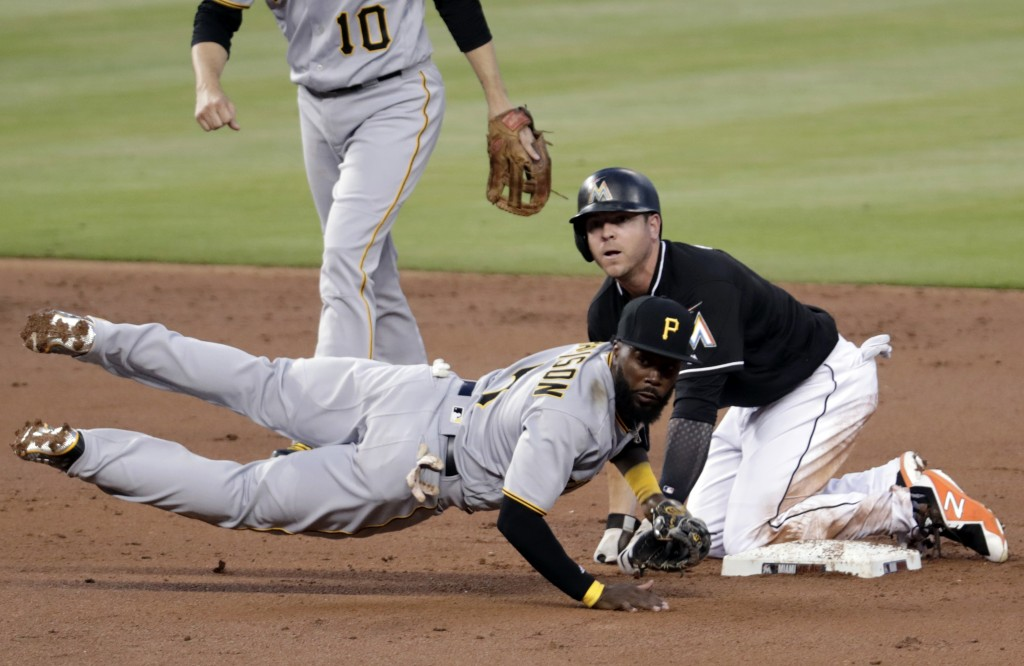 Miami Marlins' JB Shuck, right, is out at second as Pittsburgh Pirates second baseman Josh Harrison (5) throws to first during the second inning of a