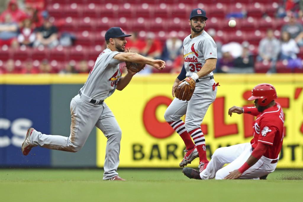 St. Louis Cardinals' Paul DeJong, left, turns a double play as Cincinnati Reds' Phillip Ervin slides into second base against St. Louis Cardinals' Gre