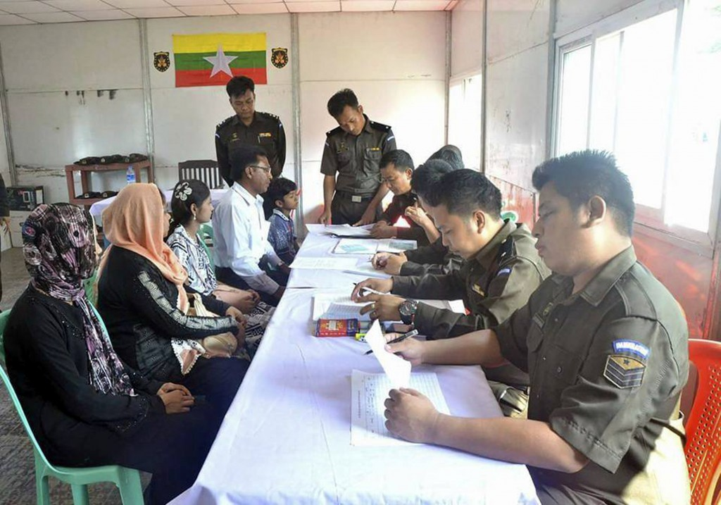 In this April 14, 2018, photo provided by  Myanmar Government Information Committee,  Myanmar immigration officials examine documents as a Rohingya fa