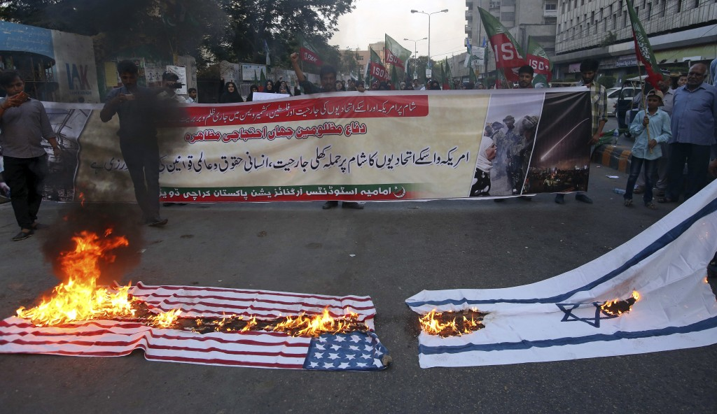 Supporters of the Imamia Students Organization, a Shiite Muslim group, chant slogans while burning representations of U.S and Israeli flags during a d