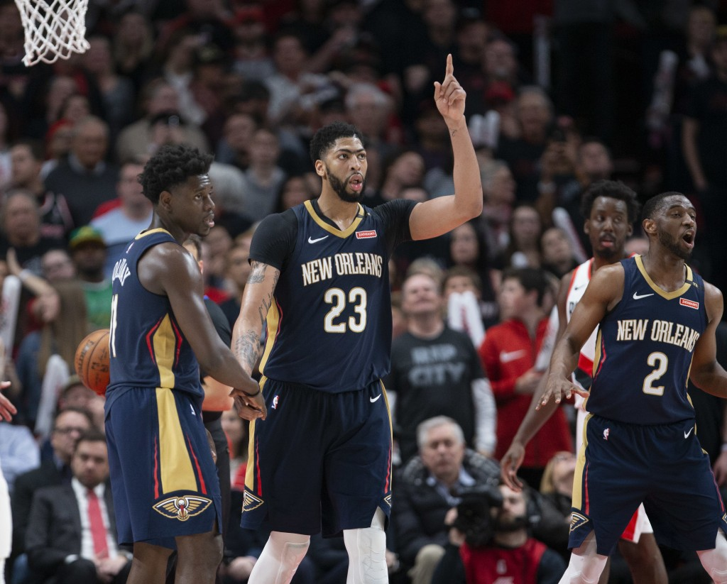 New Orleans Pelicans guard Jrue Holiday, forward Anthony Davis and guard Ian Clark celebrate a score against the Portland Trail Blazers during the sec