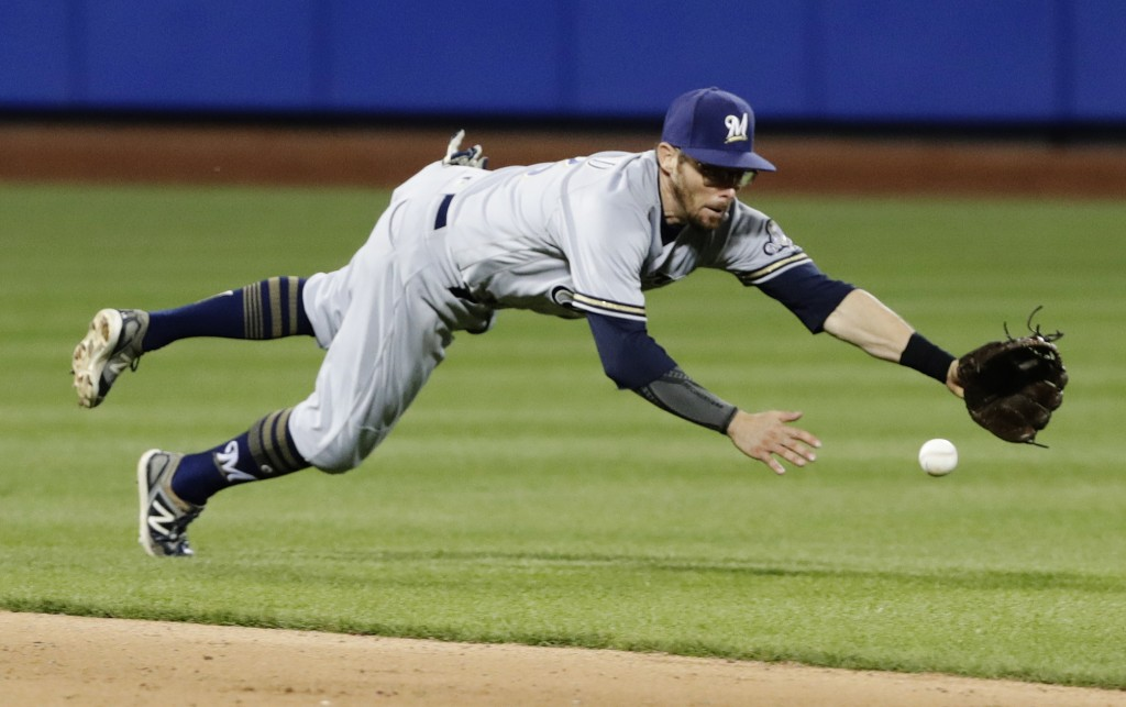 Milwaukee Brewers second baseman Eric Sogard dives for a ball hit by New York Mets' Amed Rosario for a single during the fifth inning of a baseball ga