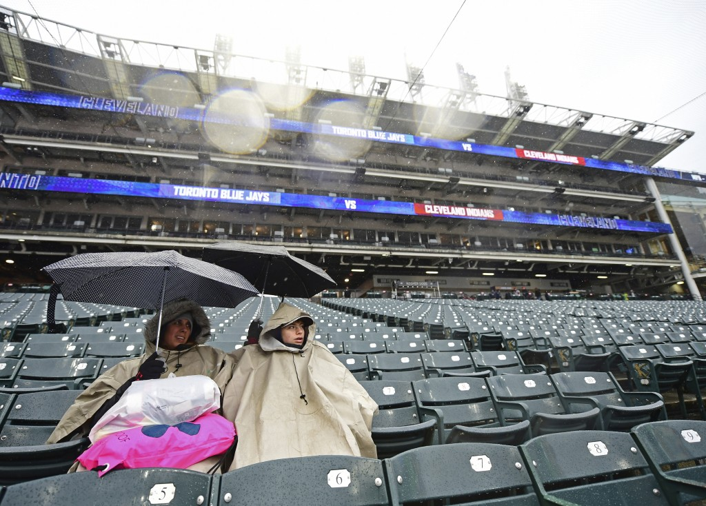 Annette and Kaden Decker sit as they wait out a rain delay in a baseball game between the Cleveland Indians and the Toronto Blue Jays, Saturday, April