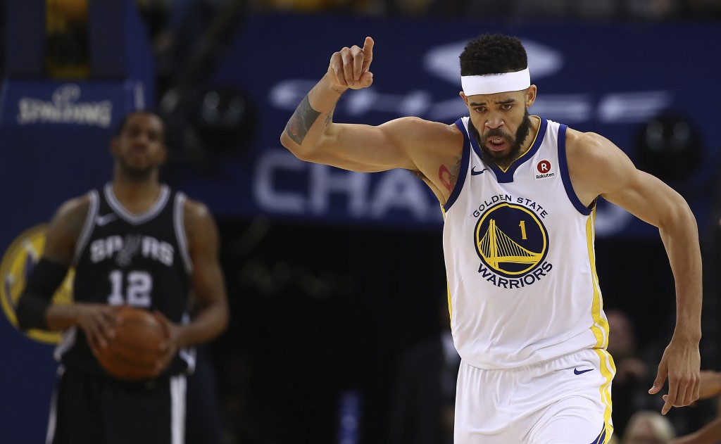 Golden State Warriors' JaVale McGee, right, celebrates a score as San Antonio Spurs' LaMarcus Aldridge (12) watches during the second half in Game 1 o