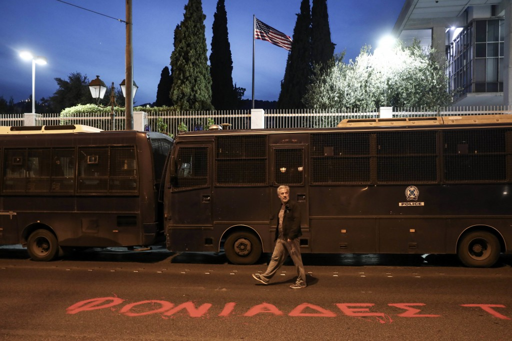 """A man walks in front of the U.S. embassy where the word """" Murderers """" is written on the street by supporters of the Greek Communist party, in Athens,"""