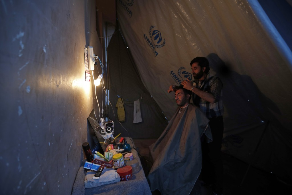 In this Friday, April 13, 2018 photo, a man who was displaced with his family from eastern Ghouta receives a haircut at a roadside makeshift barbersho