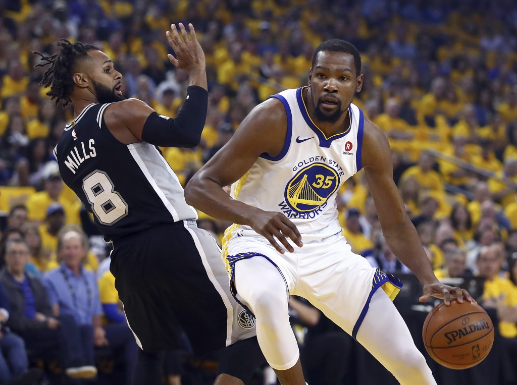 Golden State Warriors' Kevin Durant, right, drives the ball around San Antonio Spurs' Patty Mills (8) during the first half in Game 1 of a first-round