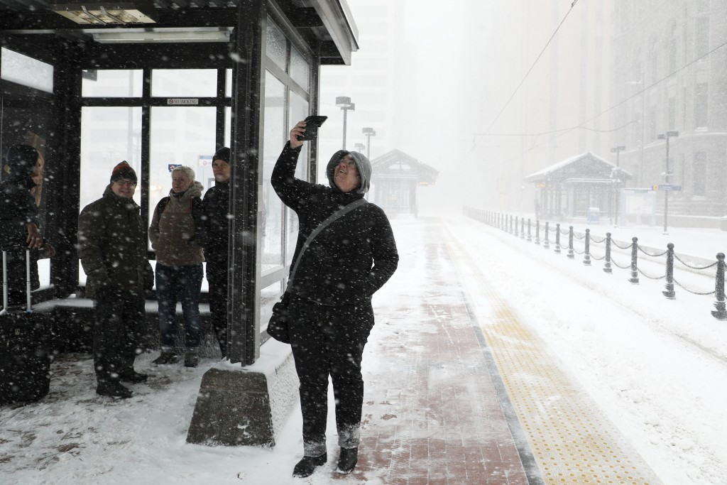 Travelers at the Metro Government Center Plaza station wait for a train as the snow picked up in downtown Minneapolis, Saturday, April 14, 2018.   The