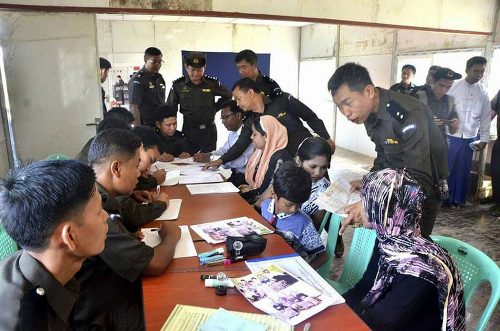 In this April 14, 2018, photo provided by  Myanmar Government Information Committee, Myanmar immigration officials examine documents and photographs w