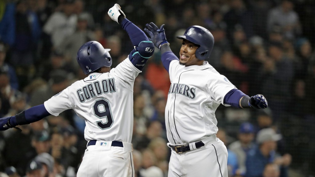 Seattle Mariners' Jean Segura, right, is cheered by Dee Gordon (9) after hitting a three-run home run against the Oakland Athletics in the second inni...