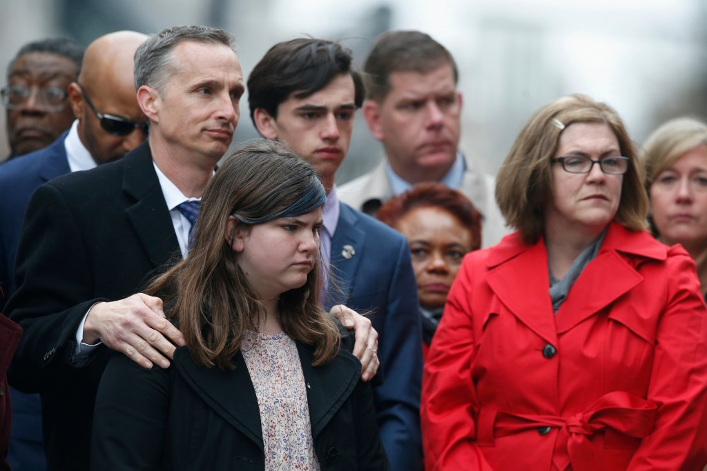 The family of Martin Richard, foreground from left, Bill, Jane, Henry and Denise, observe a moment of silence during a ceremony at the site where Mart