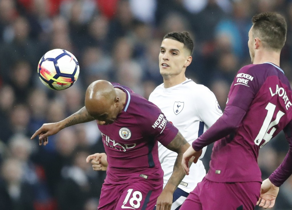 Manchester City's Fabian Delph, left, battles for the ball with Tottenham's Erik Lamela, centre, during the English Premier League soccer match betwee
