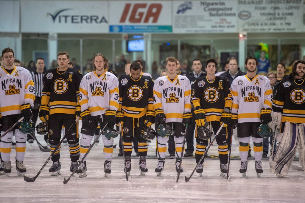 Players stand during a moment of silence to acknowledge first responders, victims, and survivors of the bus crash that killed 16 members of the Humbol