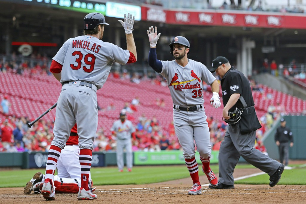 St. Louis Cardinals' Greg Garcia high fives Miles Mikolasin after hitting a home run in the second inning of a baseball game against the Cincinnati Re