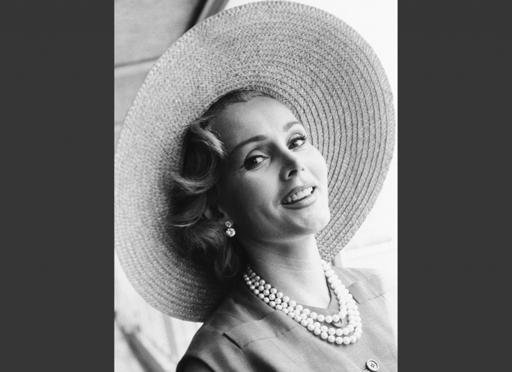 FILE - In a July 14, 1955, file photo, Zsa Zsa Gabor arrives at London Airport from Paris, in a Crimson dress and a straw hat. An auction of late actr