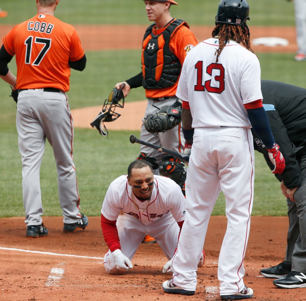 Boston Red Sox's Mookie Betts kneels on the ground in front of teammate Hanley Ramirez (13) after sliding safely into home plate during the first inni